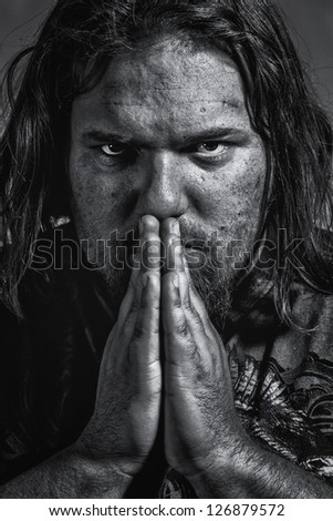 grungy, gritty looking closeup of white male praying in black and white - stock photo