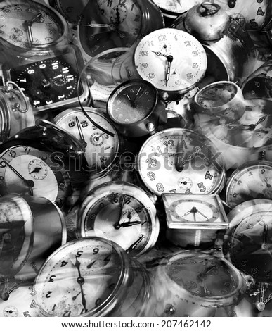 Grungy heap of alarm clocks in black and white - stock photo