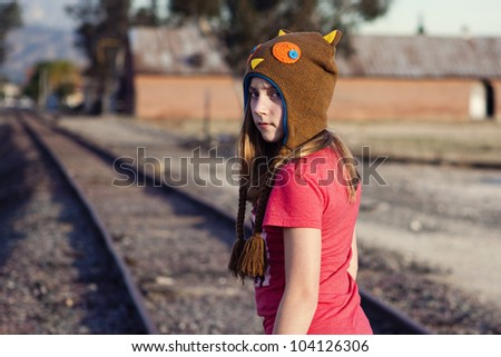 Grungy image of a teen walking on the railroad tracks