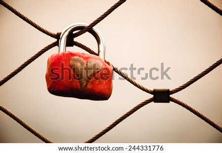 Grungy love padlock with heart decoration attached to the bridge in Paris. Valentine's day background. Toned photo. - stock photo