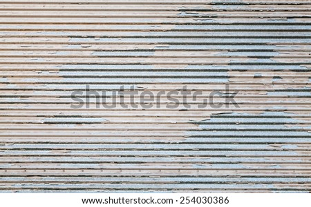 Grungy metal wall with damaged paint layer, background texture - stock photo