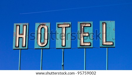Grungy old hotel sign isolated on a blue sky background with an airplane flying in the distance - stock photo