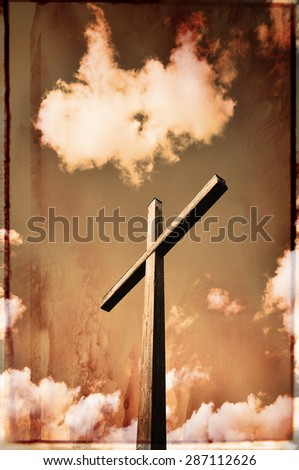 Grungy retro wooden cross among clouds. - stock photo