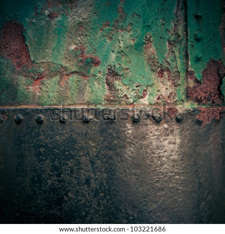 Grungy rusty old iron texture with weathered green paint and a riveted join with vignetting - stock photo