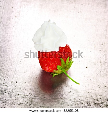 Grungy strawberry with whipped cream, still life. - stock photo