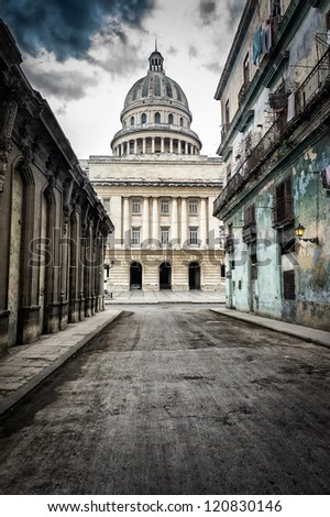 Grungy street with crumbling buildings leading to the Capitol in Old Havana - stock photo