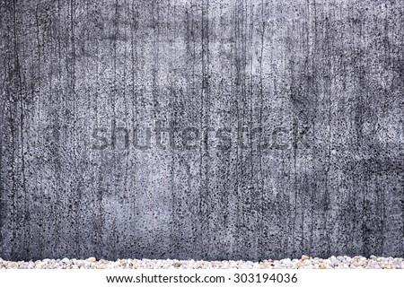 Grungy textured concrete wall for background purpose. A path with bright stones in front. - stock photo