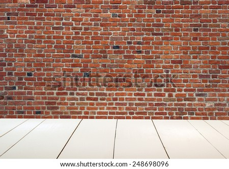 Grungy textured red brick wall with white wooden floor inside - stock photo