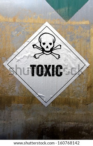 Grungy Toxic sticker label attached on rusty metal surface. - stock photo