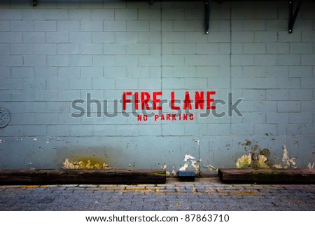 """Grungy urban alley wall with the words """"fire lane"""" posted - stock photo"""