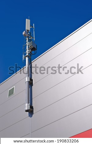 GSM Antenna. Mobile phone signal repeater system installed on the roof top of industrial building. - stock photo