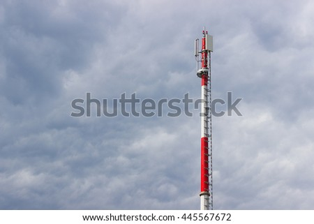 GSM antenna tower (transmitter, antenna), red and white striped pole, blue sky with clouds, horizontally. - stock photo