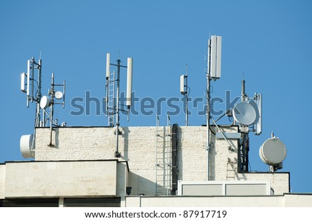 GSM transmitters on a roof of white administrative building. Close up - stock photo