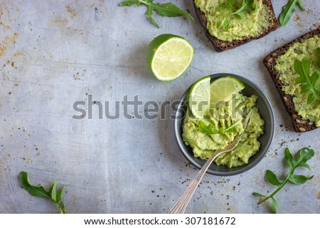 guacamole and rye toasts on rustic  background, top view, copy space - stock photo