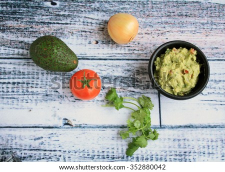 Guacamole dip in a stone black bowl with ingredients Avocado cilantro onion tomatoes on a white wood background/Guacamole top view/Holy Mole - stock photo