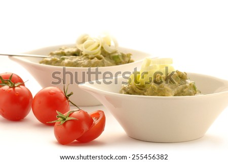 guacamole dip in bowl isolated on white background and tomato - stock photo