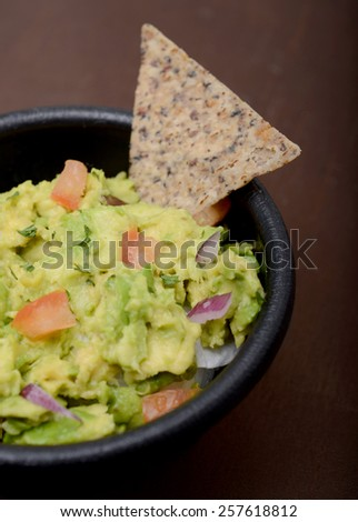 guacamole in a bowl and whole grain chip - stock photo