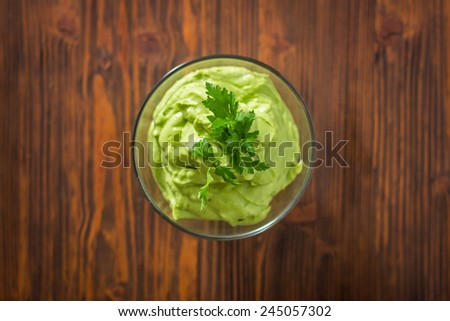 Guacamole on wooden table - stock photo