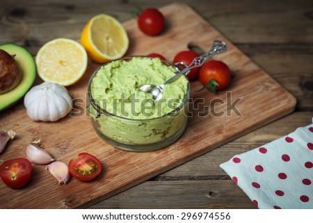 Guacamole on wooden table surrounded by its ingredients - stock photo