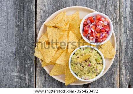 guacamole, tomato salsa and corn chips on a plate, top view closeup, horizontal - stock photo