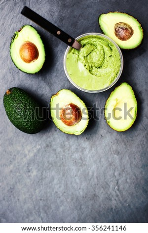 Guacamole with avocado. Halved avocado over black background with copy space for text