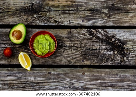 Guacamole with avocado over rustic wooden background with space for text. Top view. Food or cooking concept. - stock photo