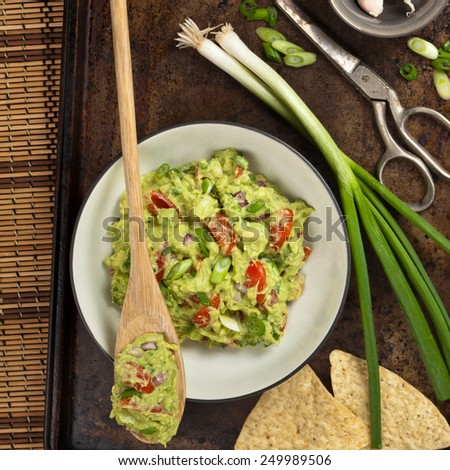 Guacamole with green onions and nachos. Selective focus. - stock photo