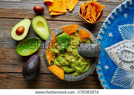 Guacamole with nachos avocado in Mexican molcajete and Sombrero hat - stock photo