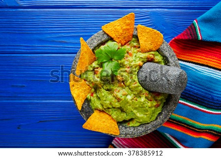 Guacamole with nachos avocado in Mexican molcajete on blue wood table - stock photo