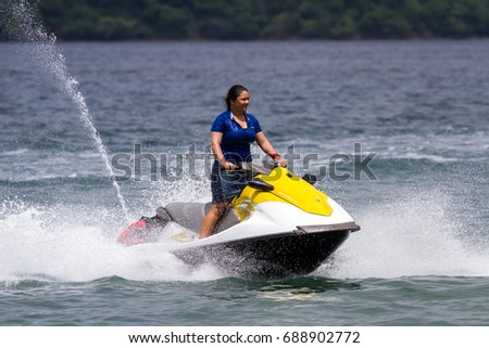 Guanacaste, Costa Rica- July 25: young woman riding a wave runner in Nacascolo Beach. July 25 2017, Guanacaste, Costa Rica.
