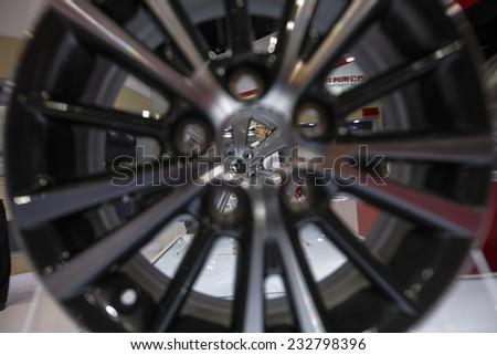 GUANGZHOU, CHINA - NOV. 20. 2014: Woman seen throe car wheel rim on the 12th China International Automobile Exhibition in Guangzhou, Guangdong province. - stock photo