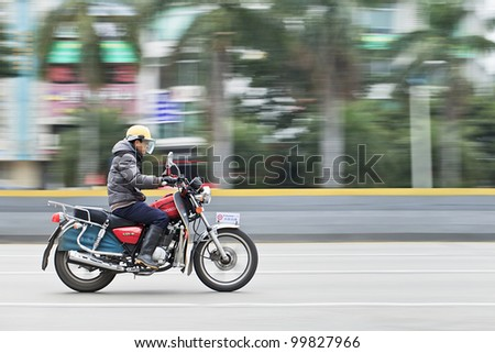GUANGZHOU-FEB. 26, 2012. Man on a Honda motorcycle on Feb. 26, 2012 in Guangzhou. Honda was founded at 24 September 1948 and has been the world's largest motorcycle manufacturer since 1959. - stock photo