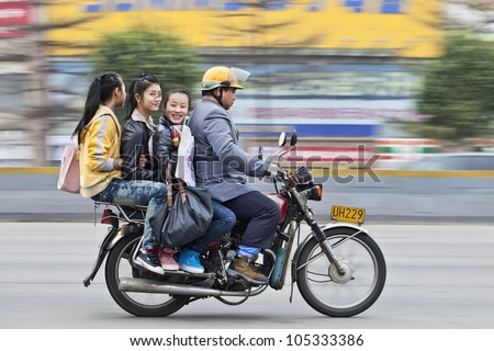 GUANGZHOU-FEB. 22, 2012. Motorcycle taxi on Feb. 22, 2012 in Guangzhou. Although the Guangzhou municipal government has banned motorcycle taxis for safety reasons it�s still a popular transport mode. - stock photo