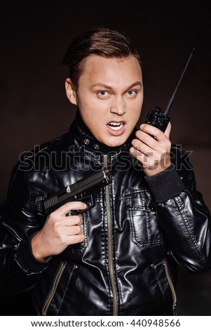 guard or  secret agent with gun calling for help by radio - stock photo