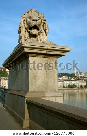 Guardian lion statue on famous Chain Bridge with Buda view in Budapest - stock photo
