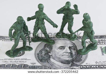 Guarding American money with green toy soldiers. - stock photo
