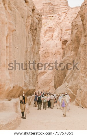 guards and tourists in chasm leading to spectacular Petra, Jordan - stock photo