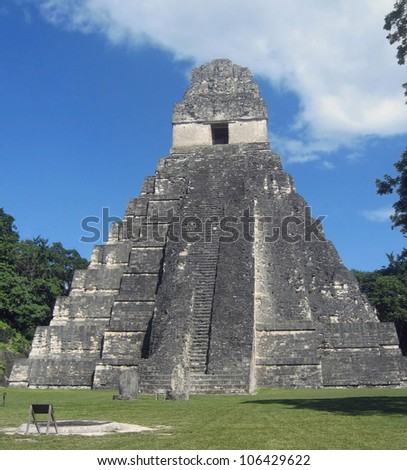 Guatemala, Tikal - Temple of the Great Jaguar. A tropical storm hovers the grand plaza of the largest Maya city. The temple dates to 730 AD and it has the tomb of king Ah Cacao, aka Jasaw Chan K'awii. - stock photo