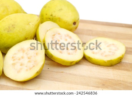 Guava Fruits And Slices Isolated on wooden board - stock photo