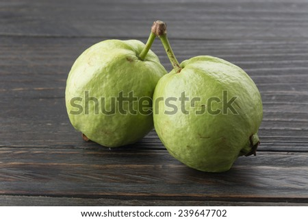 guava on black wood table - stock photo