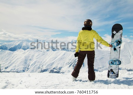 GUDAURI, GEORGIA - March 2014: Young woman wearing snowboarding helmet and mask and holding snowboard in hands, snowboarder back view in front of the mountains, Gudauri, Georgia