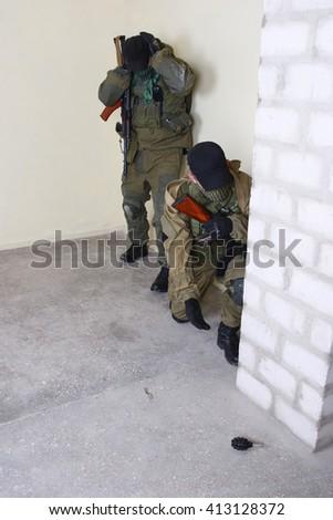 guerillas with AK-47 rifle throw a grenade inside the building - stock photo