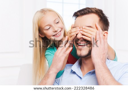 Guess who? Playful little girl covering eyes of her cheerful mother and smiling  - stock photo