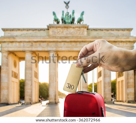 guest holding the hotel room key at Berlin with Bradenburg gate in the background - stock photo
