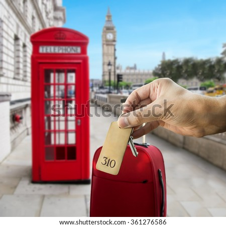 guest holding the hotel room key at London with Big Ben in the background - stock photo