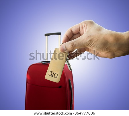 guest holding the hotel room key isolated on blue background - stock photo