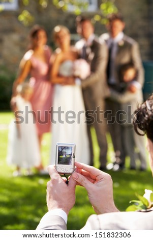 Guest Taking Photo Of Bridal Party - stock photo