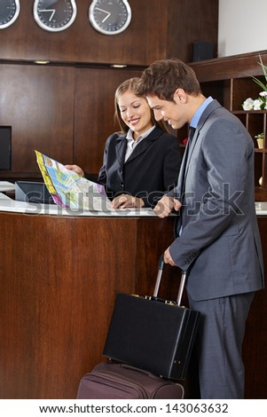 Guest with luggage looking at city map with hotel receptionist