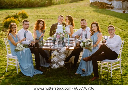 Guests at a wedding sitting at a table at sunset in nature