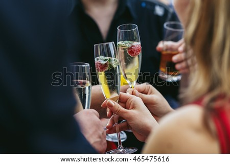 Guests clang champagne flutes with strawberries inside